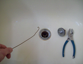 Here I am, goin' fishin' with a coat hanger. It's one DIY way to unclog a bathtub drain. --Phil
